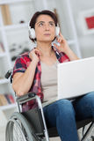 Woman in wheelchair enjoys music in headphones Royalty Free Stock Photos