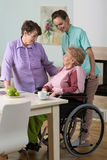 Woman on wheelchair, friend and nurse Stock Image