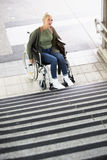 Woman in a wheelchair in front of stairs. Woman in wheelchair in front of stairs outside Stock Photos