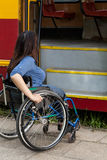 Woman of wheelchair having problem with public transport. Vertical Royalty Free Stock Photography