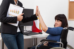 Woman on wheelchair and her co-worker Royalty Free Stock Image