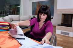 Woman on wheelchair during ironing Royalty Free Stock Photo