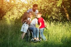 Woman in wheelchair kisses her son among family members. Cheerful Woman In Wheelchair Kisses Her Pretty Little Daughter And Hugs Son While Caring Man Looks royalty free stock photo