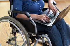 Woman on a wheelchair with laptop Stock Photography
