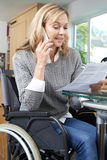 Woman In Wheelchair Making Phone Call Whilst Reading Letter Stock Image