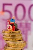 Woman in wheelchair on money stack Royalty Free Stock Image