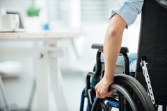 Woman in wheelchair. Next to an office desk, hand close up, unrecognizable person Royalty Free Stock Photos