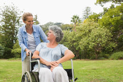 Woman in wheelchair in park with daughter Stock Photo