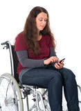 Woman in wheelchair with phone Royalty Free Stock Images
