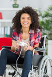 Woman in wheelchair playing video game Stock Images