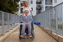 Woman with wheelchair on ramp. Happy woman in wheelchair on a ramp Royalty Free Stock Image