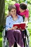Woman on wheelchair reading book Stock Photos