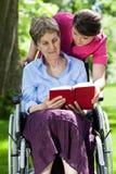 Woman on wheelchair reading book Stock Photos