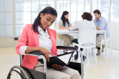 Woman in wheelchair reading document with colleauges in background Royalty Free Stock Photos