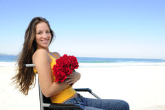 Woman in wheelchair with red roses Stock Photos