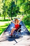 Woman on a wheelchair rising her crutches Stock Images
