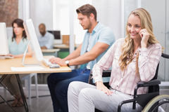 Woman in wheelchair smiles to camera in front of people working Stock Image