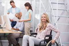 Woman in wheelchair smiling at camera with team behind her Stock Image