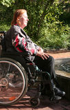 Woman in wheelchair taking a sunbath Royalty Free Stock Photos