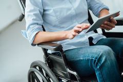 Woman in wheelchair using a tablet Stock Image