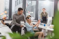 Woman in wheelchair using virtual reality glasses. At modern office Stock Images