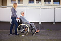 Woman in wheelchair on the way Stock Photos