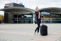 Woman With Wheeled Luggage Standing Outside Railroad Station Royalty Free Stock Image