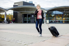 Woman With Wheeled Luggage Walking Outside Train Station Royalty Free Stock Photos