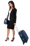 Woman wheeling a suitcase. Woman in a skirt suit wheeling a suitcase Stock Photography