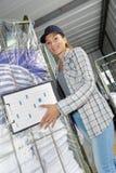 Woman wheeling trolley clean laundry. Woman wheeling trolley of clean laundry Royalty Free Stock Photos