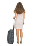 Woman with wheels suitcase. Rear view Royalty Free Stock Image