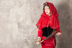 Woman with a whip. Beautiful young woman with a whip near the wall royalty free stock image