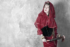 Woman with a whip. Beautiful young woman with a whip near the wall Royalty Free Stock Images
