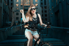 Woman with whip on a bicycle. Royalty Free Stock Photos