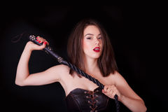 Woman with a whip in her hand. Woman on a black background with a whip in her hand Stock Images
