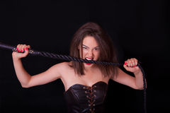 Woman with a whip in her hand. Woman on a black background with a whip in her hand Royalty Free Stock Photos