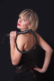 Woman with a whip in her hand. Woman on a black background with a whip in her hand Royalty Free Stock Images