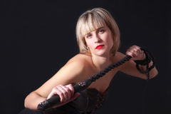 Woman with a whip in her hand. Woman on a black background with a whip in her hand Stock Photo