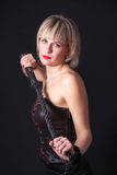 Woman with a whip in her hand. Woman on a black background with a whip in her hand Stock Photography