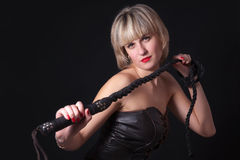 Woman with a whip in her hand. Woman on a black background with a whip in her hand Stock Photos