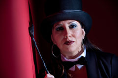 Woman with whip wearing a top hat. Woman dressed like a circus ringmaster with leather crop Royalty Free Stock Photography