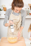 Woman whipping with electric mixer Royalty Free Stock Photos