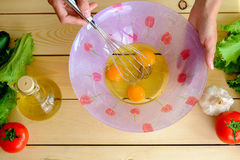 Woman whisking the eggs in a bowl with a beater Stock Photo