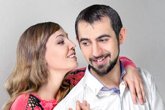 Woman whisper to boyfriend putting a hand on his shoulder Royalty Free Stock Photography