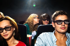 Woman Whispering In Boyfriend's Ear In Cinema Theatre Stock Photos