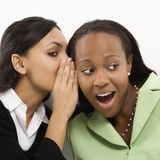Woman whispering in ear. Indian young adult woman whispering in ear of mid-adult African-American woman royalty free stock images