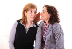 Woman whispering gossip in an other woman ear Royalty Free Stock Photos