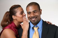 Woman whispering in husband's ear stock photography