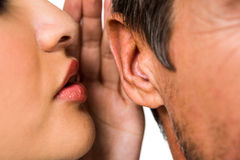 Woman whispering in man ear Stock Image