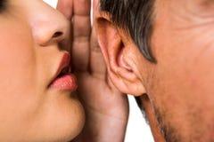 Woman whispering in man ear Stock Image